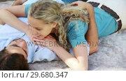 Купить «A man lies on the ground as his girlfriend lies down on his chest», видеоролик № 29680347, снято 17 ноября 2011 г. (c) Wavebreak Media / Фотобанк Лори