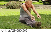 Купить «A woman stretches out in the park», видеоролик № 29680363, снято 17 ноября 2011 г. (c) Wavebreak Media / Фотобанк Лори