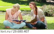 Купить «Two ladies reading in the park as they then look at the camera», видеоролик № 29680407, снято 17 ноября 2011 г. (c) Wavebreak Media / Фотобанк Лори