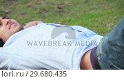 Купить «Camera pans across to show a man lying on the ground listening to music», видеоролик № 29680435, снято 17 ноября 2011 г. (c) Wavebreak Media / Фотобанк Лори