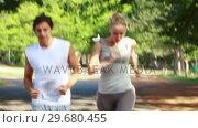 Купить «Smiling couple jog together as time elapses and they are further down the road», видеоролик № 29680455, снято 17 ноября 2011 г. (c) Wavebreak Media / Фотобанк Лори