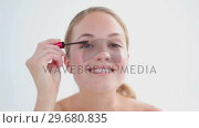 Купить «Smiling blonde applying mascara on her eyelashes», видеоролик № 29680835, снято 22 ноября 2011 г. (c) Wavebreak Media / Фотобанк Лори