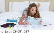 Купить «Serious young woman studying while lying», видеоролик № 29681327, снято 23 ноября 2011 г. (c) Wavebreak Media / Фотобанк Лори