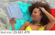 Купить «Tanned woman reading a novel», видеоролик № 29681479, снято 18 ноября 2011 г. (c) Wavebreak Media / Фотобанк Лори