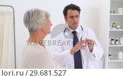 Купить «Doctor going to give an injection to a patient», видеоролик № 29681527, снято 25 ноября 2011 г. (c) Wavebreak Media / Фотобанк Лори