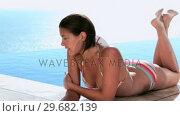 Купить «Woman lying on the edge of swimming pool», видеоролик № 29682139, снято 7 ноября 2011 г. (c) Wavebreak Media / Фотобанк Лори