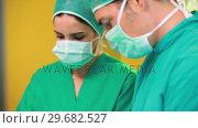 Купить «Surgeons wearing a surgical equipment», видеоролик № 29682527, снято 24 апреля 2012 г. (c) Wavebreak Media / Фотобанк Лори