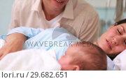 Купить «Father looking at his wife and a newborn baby sleeping», видеоролик № 29682651, снято 27 апреля 2012 г. (c) Wavebreak Media / Фотобанк Лори