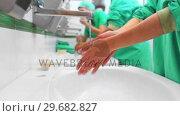 Купить «Surgical team washing hands», видеоролик № 29682827, снято 24 апреля 2012 г. (c) Wavebreak Media / Фотобанк Лори