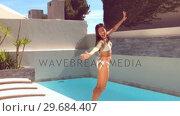 Купить «Pretty woman jumping into swimming pool», видеоролик № 29684407, снято 25 марта 2013 г. (c) Wavebreak Media / Фотобанк Лори