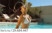 Купить «Woman in swimming pool tossing her wet hair », видеоролик № 29684447, снято 25 марта 2013 г. (c) Wavebreak Media / Фотобанк Лори
