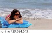 Купить «Girl sunbathing on a lilo on the beach», видеоролик № 29684543, снято 3 апреля 2013 г. (c) Wavebreak Media / Фотобанк Лори