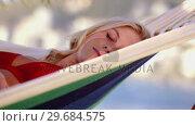 Купить «Pretty blonde woman sleeping on a hammock», видеоролик № 29684575, снято 3 апреля 2013 г. (c) Wavebreak Media / Фотобанк Лори