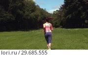 Купить «Sporty brunette jogging on a lawn», видеоролик № 29685555, снято 5 июля 2013 г. (c) Wavebreak Media / Фотобанк Лори