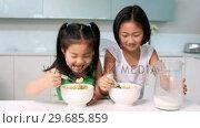 Купить «Two happy girls eating cereal», видеоролик № 29685859, снято 29 августа 2013 г. (c) Wavebreak Media / Фотобанк Лори