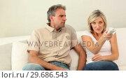 Купить «Woman stealing the remote control from her sleeping husband on the couch», видеоролик № 29686543, снято 17 октября 2013 г. (c) Wavebreak Media / Фотобанк Лори