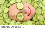 Купить «Smiling womans face surrounded by cucumber slices », видеоролик № 29686619, снято 23 июля 2013 г. (c) Wavebreak Media / Фотобанк Лори