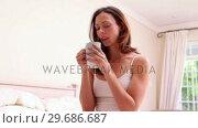 Купить «Smiling brunette drinking coffee», видеоролик № 29686687, снято 12 декабря 2013 г. (c) Wavebreak Media / Фотобанк Лори