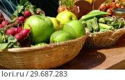 Купить «Close-up of harvested fruits and vegetable in wicker basket in field», видеоролик № 29687283, снято 16 февраля 2016 г. (c) Wavebreak Media / Фотобанк Лори