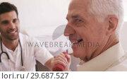 Купить «Male doctor assisting senior man to exercise», видеоролик № 29687527, снято 2 марта 2016 г. (c) Wavebreak Media / Фотобанк Лори