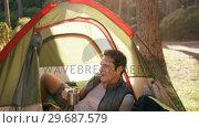 Купить «Man lying in tent and having coffee», видеоролик № 29687579, снято 9 февраля 2016 г. (c) Wavebreak Media / Фотобанк Лори