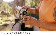 Купить «Man pouring the drinking water in cup at campsite», видеоролик № 29687627, снято 9 февраля 2016 г. (c) Wavebreak Media / Фотобанк Лори