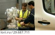 Купить «Man delivering courier to warehouse worker», видеоролик № 29687711, снято 17 октября 2015 г. (c) Wavebreak Media / Фотобанк Лори