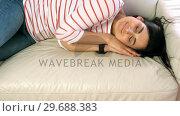 Woman falling asleep on the couch in living room. Стоковое видео, агентство Wavebreak Media / Фотобанк Лори