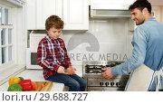 Купить «Boy helping father while cooking food in kitchen», видеоролик № 29688727, снято 28 июня 2016 г. (c) Wavebreak Media / Фотобанк Лори
