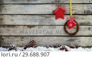 Купить «Wreath and heart shape decoration hanging on a plank», видеоролик № 29688907, снято 30 августа 2016 г. (c) Wavebreak Media / Фотобанк Лори