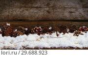 Купить «Pine cones decoration on fake snow», видеоролик № 29688923, снято 30 августа 2016 г. (c) Wavebreak Media / Фотобанк Лори