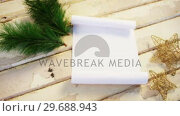 Купить «Christmas fir, star and paper on wooden plank», видеоролик № 29688943, снято 30 августа 2016 г. (c) Wavebreak Media / Фотобанк Лори