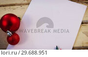 Купить «Christmas bauble, felt pen and paper on wooden plank», видеоролик № 29688951, снято 30 августа 2016 г. (c) Wavebreak Media / Фотобанк Лори