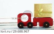 Купить «Toy tempo carrying christmas present against white background», видеоролик № 29688967, снято 30 августа 2016 г. (c) Wavebreak Media / Фотобанк Лори