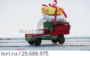 Купить «Toy tempo carrying christmas present on wooden plank», видеоролик № 29688975, снято 30 августа 2016 г. (c) Wavebreak Media / Фотобанк Лори