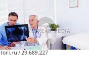 Купить «Male doctor and coworker examining x-ray», видеоролик № 29689227, снято 25 августа 2016 г. (c) Wavebreak Media / Фотобанк Лори