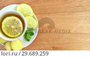 Купить «Lemon tea with sliced ginger and herb», видеоролик № 29689259, снято 8 июня 2016 г. (c) Wavebreak Media / Фотобанк Лори
