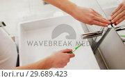 Купить «Woman washing toothbrush under sink in bathroom», видеоролик № 29689423, снято 26 августа 2016 г. (c) Wavebreak Media / Фотобанк Лори
