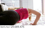 Купить «Woman doing exercise in living room», видеоролик № 29689475, снято 26 августа 2016 г. (c) Wavebreak Media / Фотобанк Лори