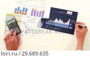 Купить «Man hand calculating the graph», видеоролик № 29689635, снято 24 августа 2016 г. (c) Wavebreak Media / Фотобанк Лори