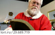 Купить «Santa claus reading a list during christmas time», видеоролик № 29689719, снято 6 июня 2016 г. (c) Wavebreak Media / Фотобанк Лори
