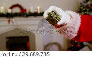 Купить «Santa claus holding gift box», видеоролик № 29689735, снято 6 июня 2016 г. (c) Wavebreak Media / Фотобанк Лори