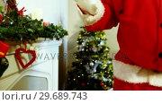 Купить «Mid section of santa claus placing gift box on fireplace», видеоролик № 29689743, снято 6 июня 2016 г. (c) Wavebreak Media / Фотобанк Лори