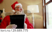 Купить «Santa claus looking through window while using digital tablet», видеоролик № 29689775, снято 6 июня 2016 г. (c) Wavebreak Media / Фотобанк Лори