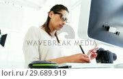 Купить «Graphic designer using a graphics tablet», видеоролик № 29689919, снято 1 сентября 2016 г. (c) Wavebreak Media / Фотобанк Лори