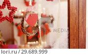 Купить «Christmas decoration hanging on window», видеоролик № 29689999, снято 31 августа 2016 г. (c) Wavebreak Media / Фотобанк Лори