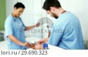 Купить «Doctors treating a patient», видеоролик № 29690323, снято 11 сентября 2016 г. (c) Wavebreak Media / Фотобанк Лори