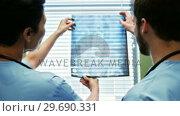Купить «Two doctor studying a x-ray», видеоролик № 29690331, снято 11 сентября 2016 г. (c) Wavebreak Media / Фотобанк Лори