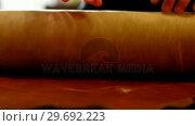 Купить «Mid-section of craftswoman rolling up the sheet of leather on work tool», видеоролик № 29692223, снято 29 сентября 2016 г. (c) Wavebreak Media / Фотобанк Лори