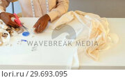 Купить «Female fashion designer preparing thread to stitch couture», видеоролик № 29693095, снято 23 августа 2016 г. (c) Wavebreak Media / Фотобанк Лори
